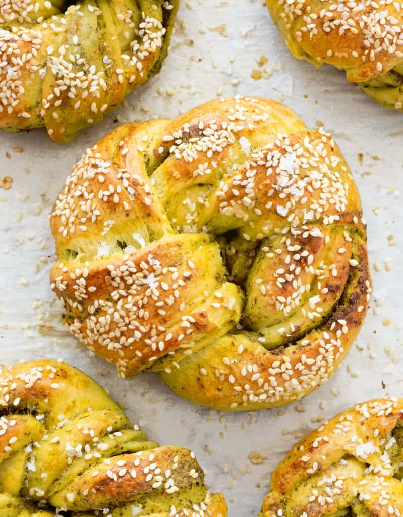 Top view of a large pesto bread knot  with sesame seeds over white parchment paper.