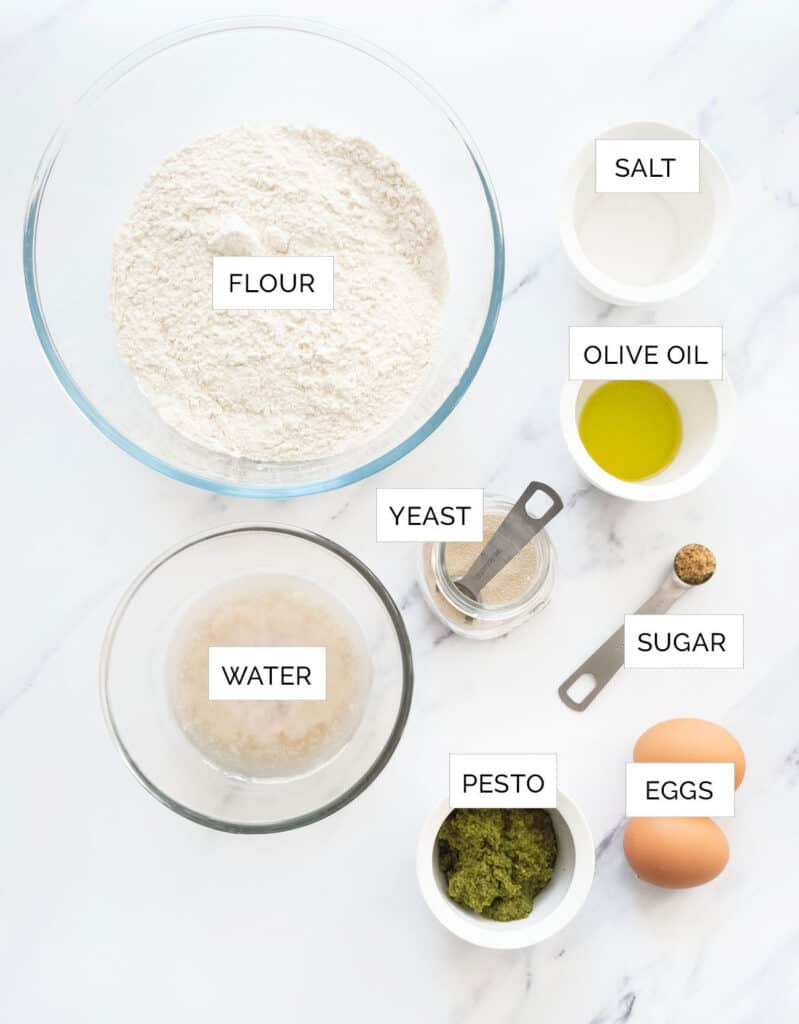 The pesto bread ingredients are arranged over a white background.