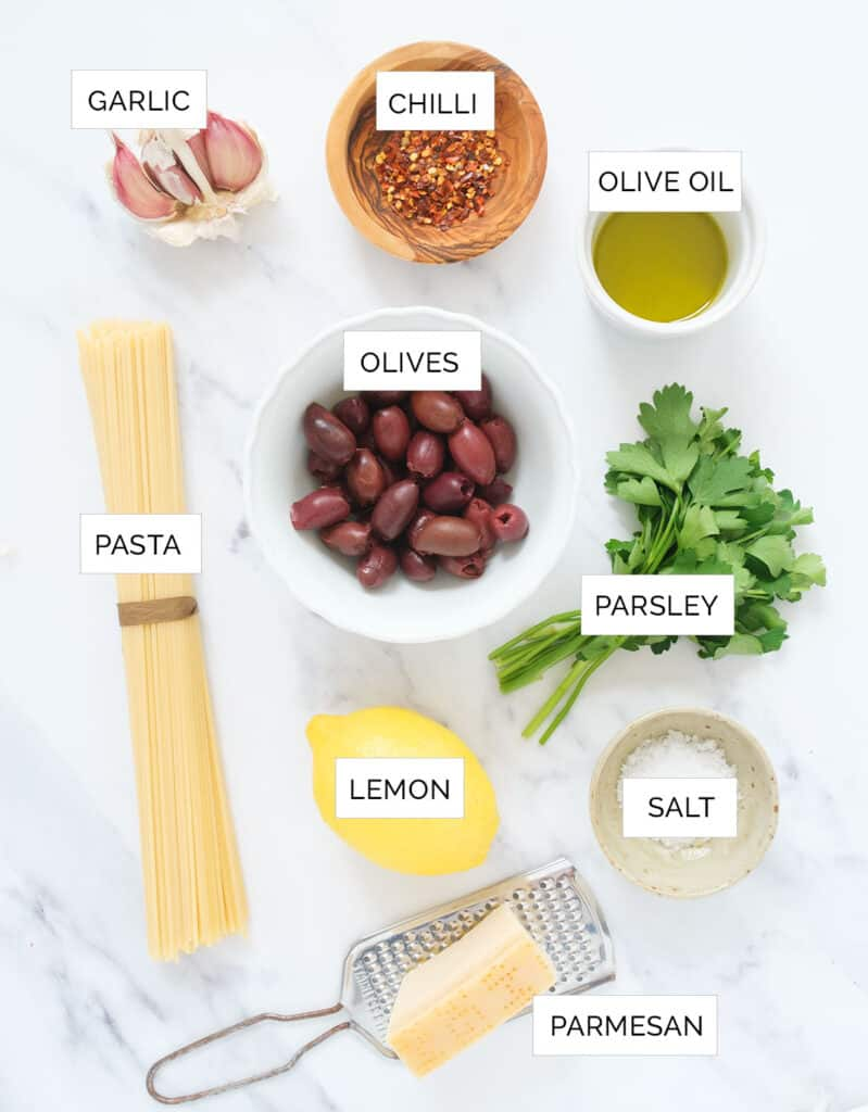 The ingredients to make this easy pasta with olives are arranged over a white background.