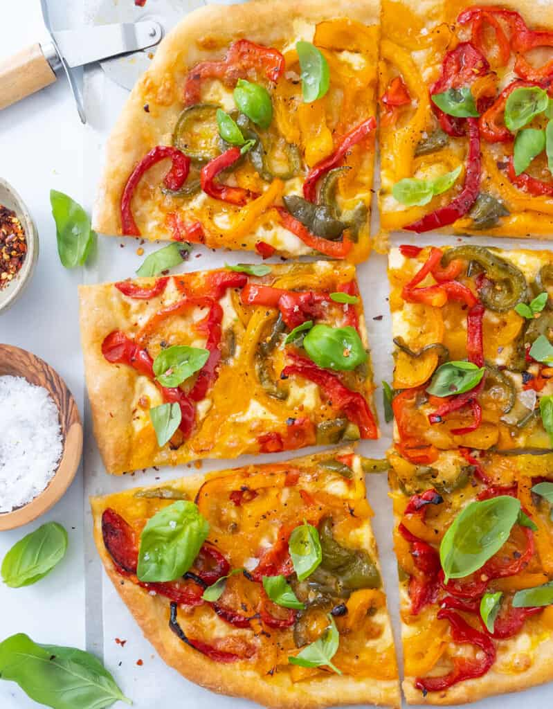Top view of a large pizza with peppers cut into slices and garnished with basil leaves.