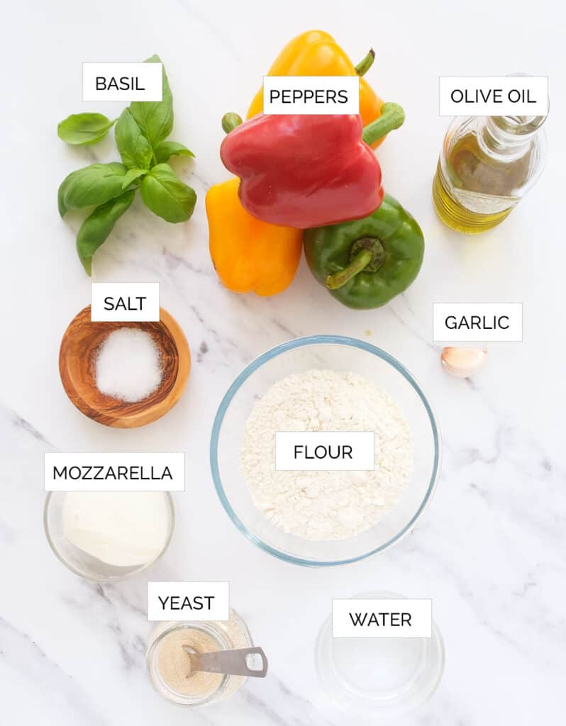 The ingredients to make pizza with peppers are arranged over a white background.