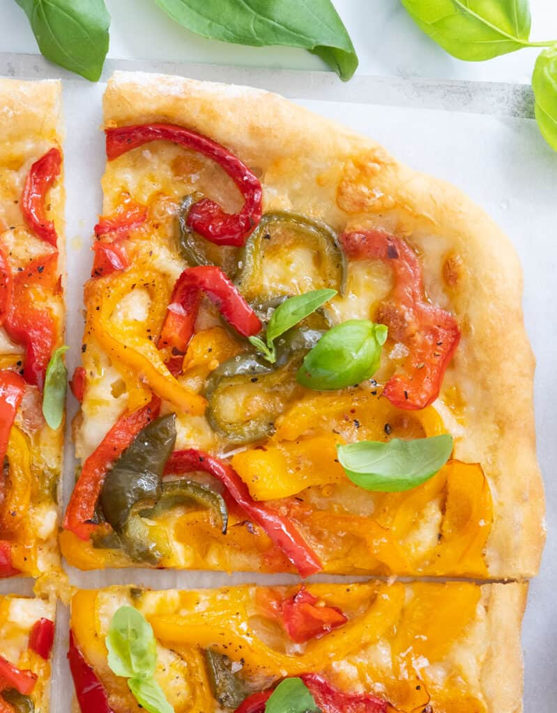 Top view of a slice of pizza with peppers and fresh basil leaves.