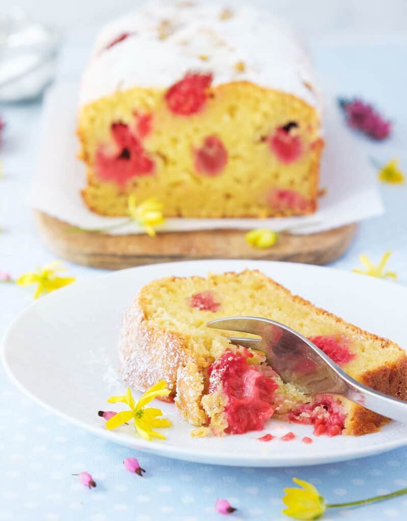 Close-up of a slice of raspberry ricotta cake with a for, small flowers and the whole cake loaf in the background.
