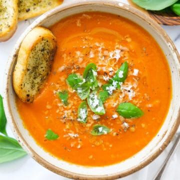Top view of a bowl full of tomato soup with potato garnished with basil leaves.