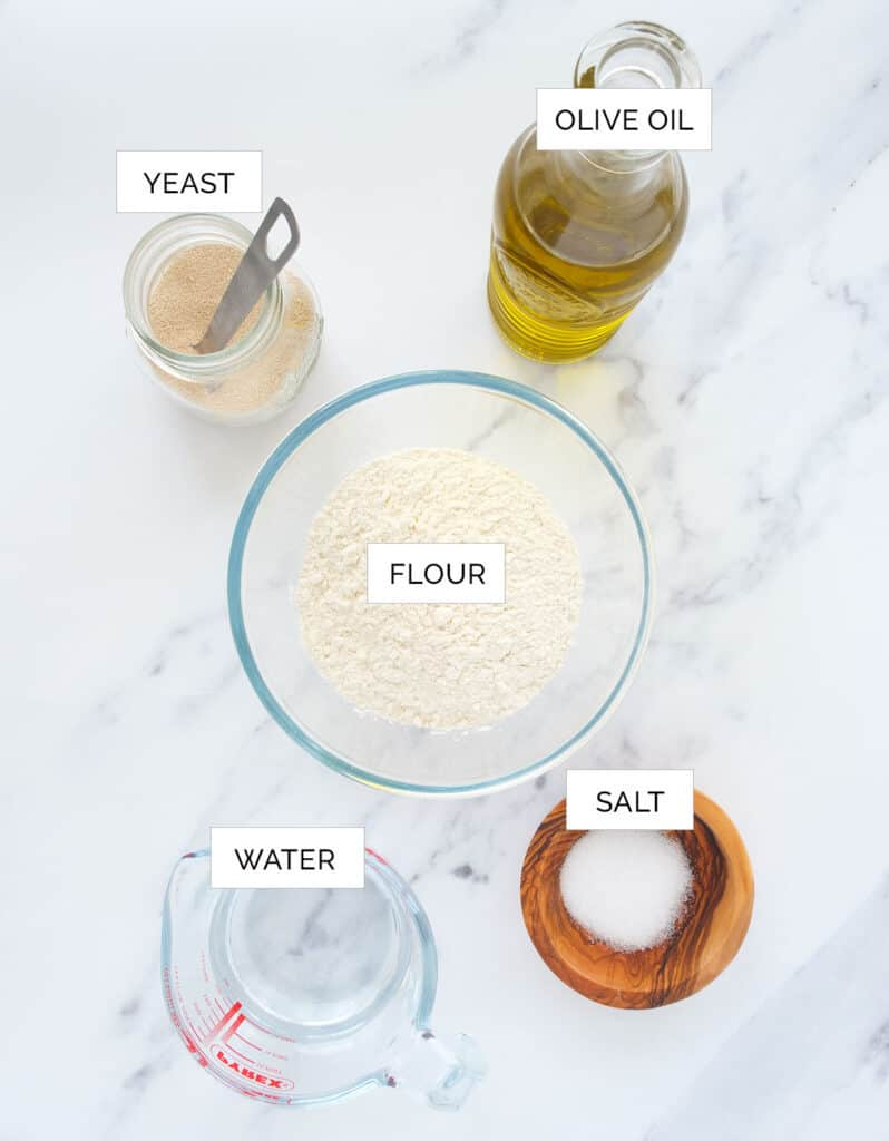 The ingredients to make this easu no-knead pizza dough are arranged over a white background.