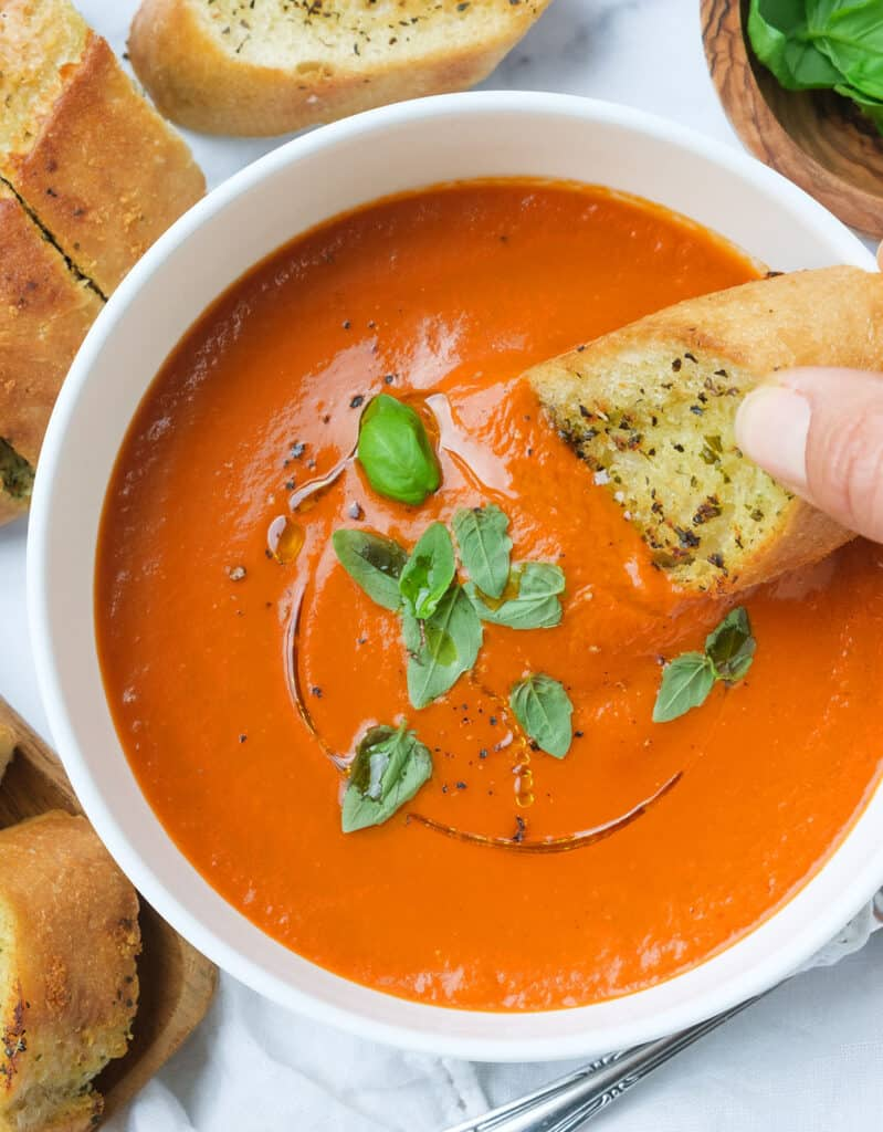 Top view of a white bowl full of easy tomato soup garnished with fresh basil leaves and served with crusty bread.