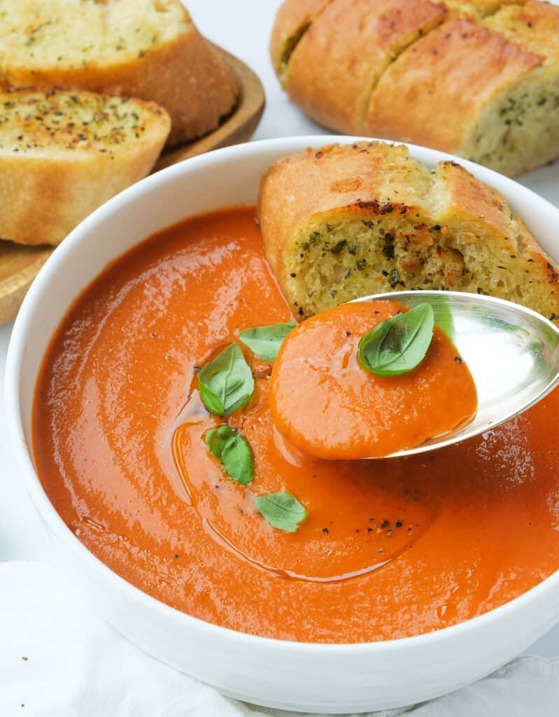 A spoon and a white bowl full of easy tomato soup served with crusty garlic bread.