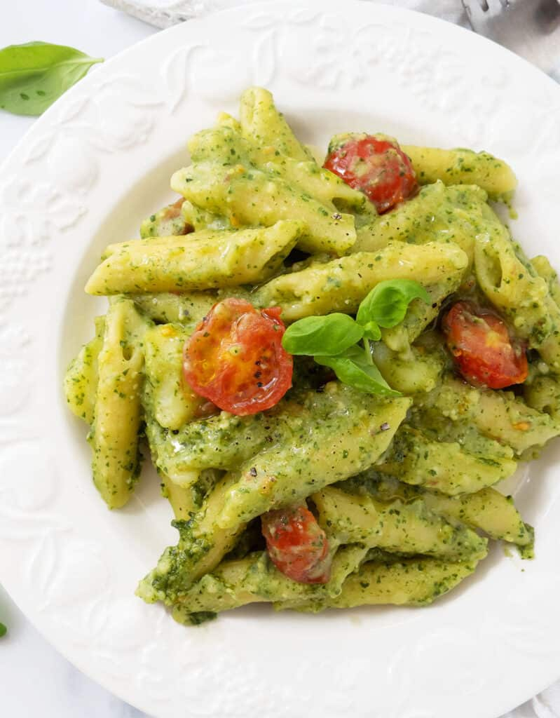 Top view of a white plate full of penne with pesto, potatoes, abd cherry tomatoes cooked together in one pot.
