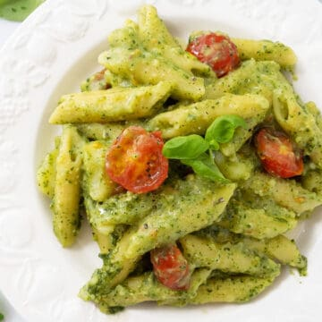 Top view of a white plate full of penne with pesto and cherry tomatoes.