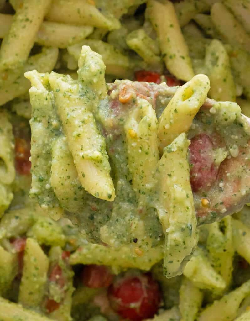 A wooden spoon full of penne with pesto.
