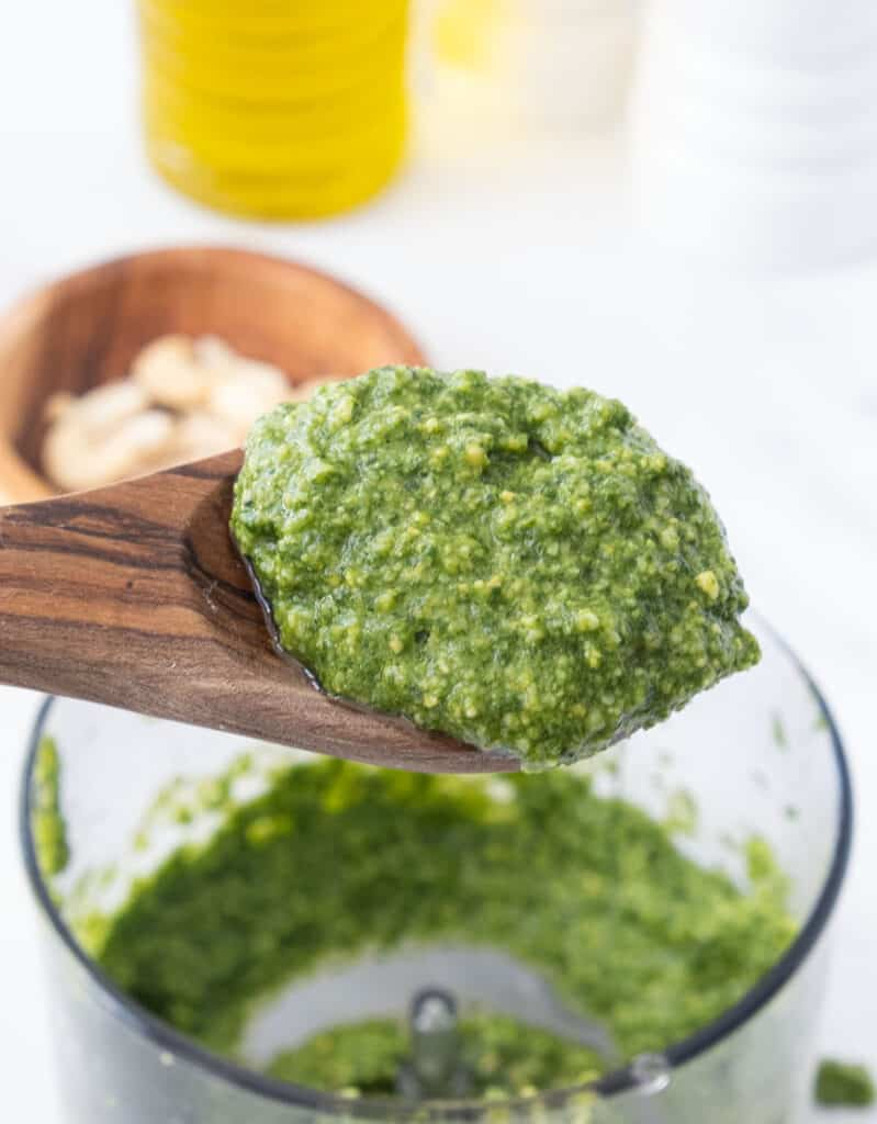 Close-up of a wooden spoon full of basil pesto.