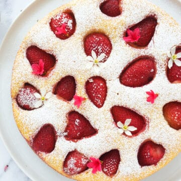 Top view of a round strawberry ricotta cake dusted with powdered sugar over a white background.
