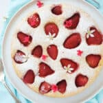 Top view of a round strawberry ricotta cake over a tourquois background.