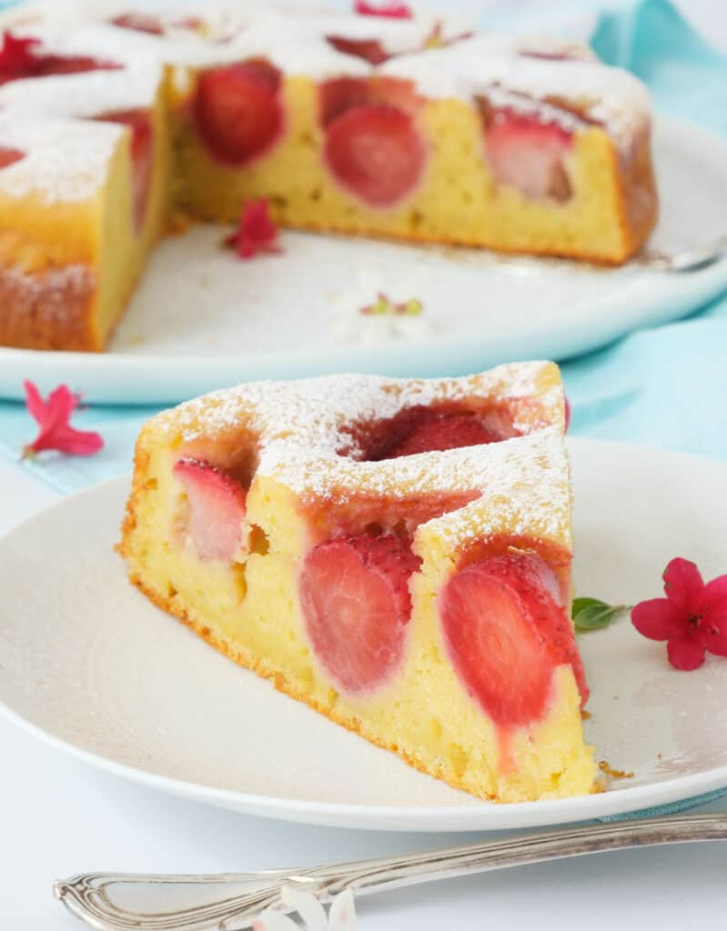 Close-up of a slice of strawberry ricotta cake on a white dessert plate while the rest of the cake is in the background.