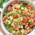 Top view of a white salad bowl full of barley salad with cherry tomatoes , diced cucumber and fresh herbs.