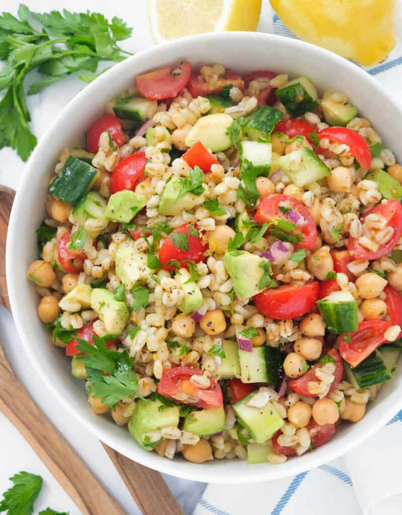 Top view of a white salad bowl full of barley salad with cherry tomatoes, diced cucumber and herbs.