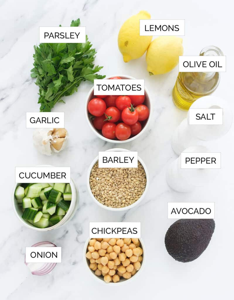 The ingredients to make the barley salad are arranged over a white background.
