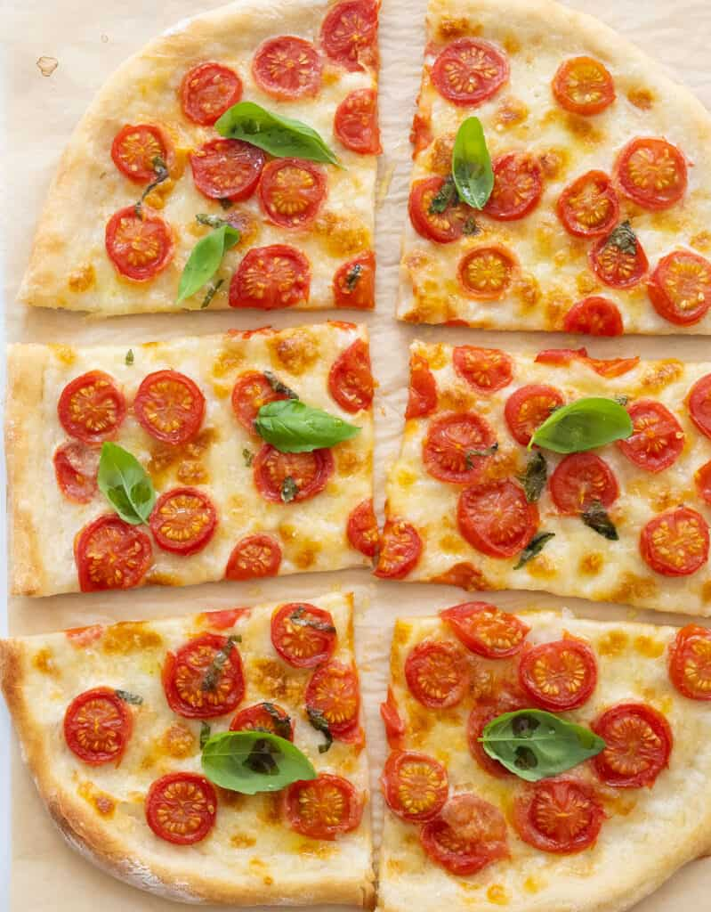 Top view of a whole fresh tomato pizza cut into slices and garnished with fresh basil leaves.