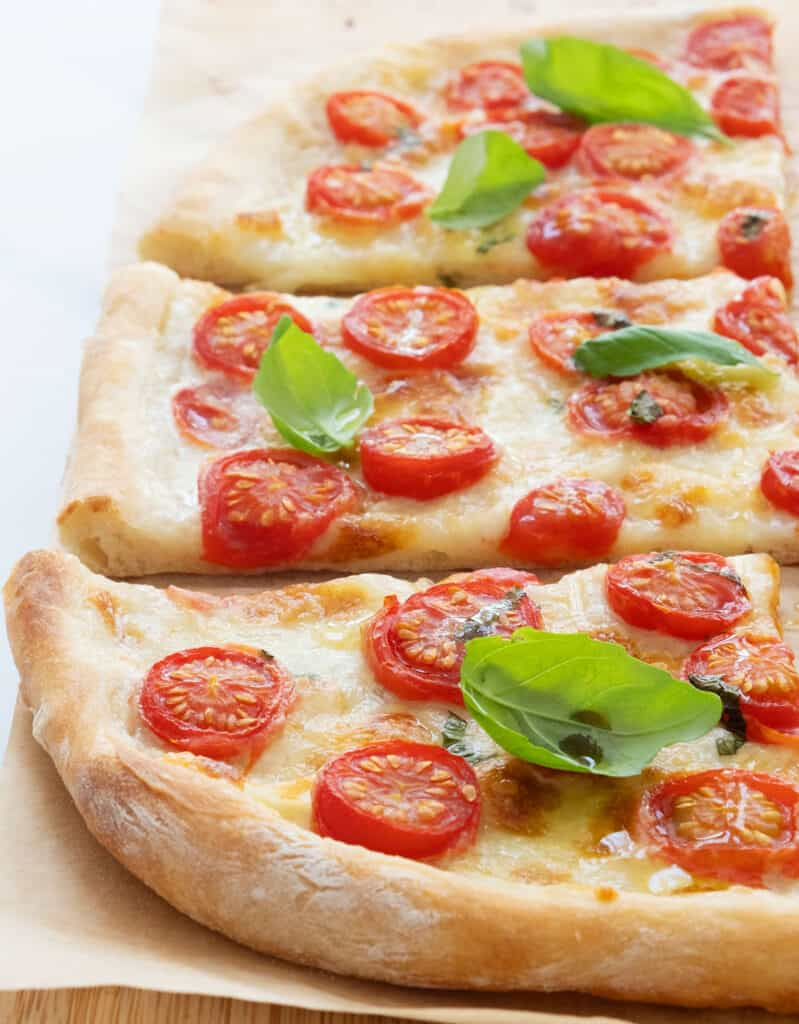 Close-up of a few slices of crusty pizza with fresh cherry tomatoes and basil leaves.