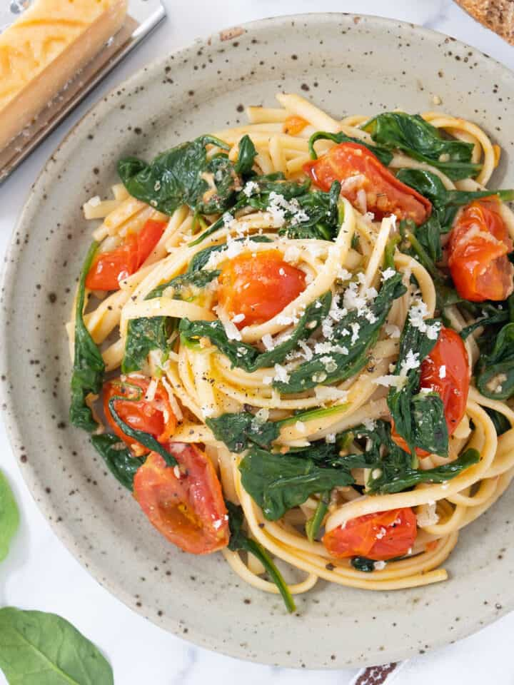 Top view of a grey plate with pasta with tomatoes and spinach.