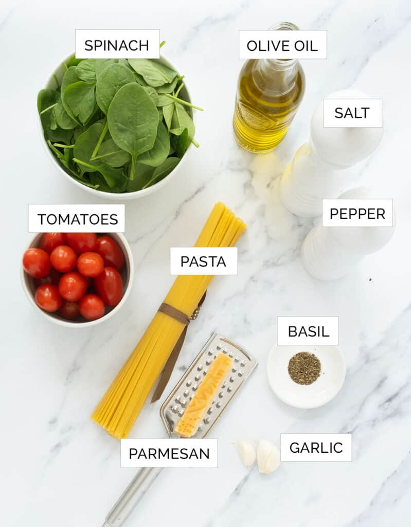 The ingredients to make this pasta with tomatoes and spinach are arranged over a white table.