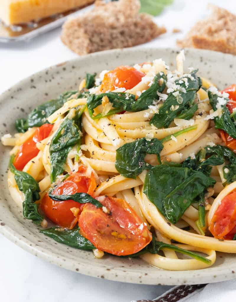 Close-up of a grey plate full of pasta with tomatoes and spinach served with grated parmesan cheese.