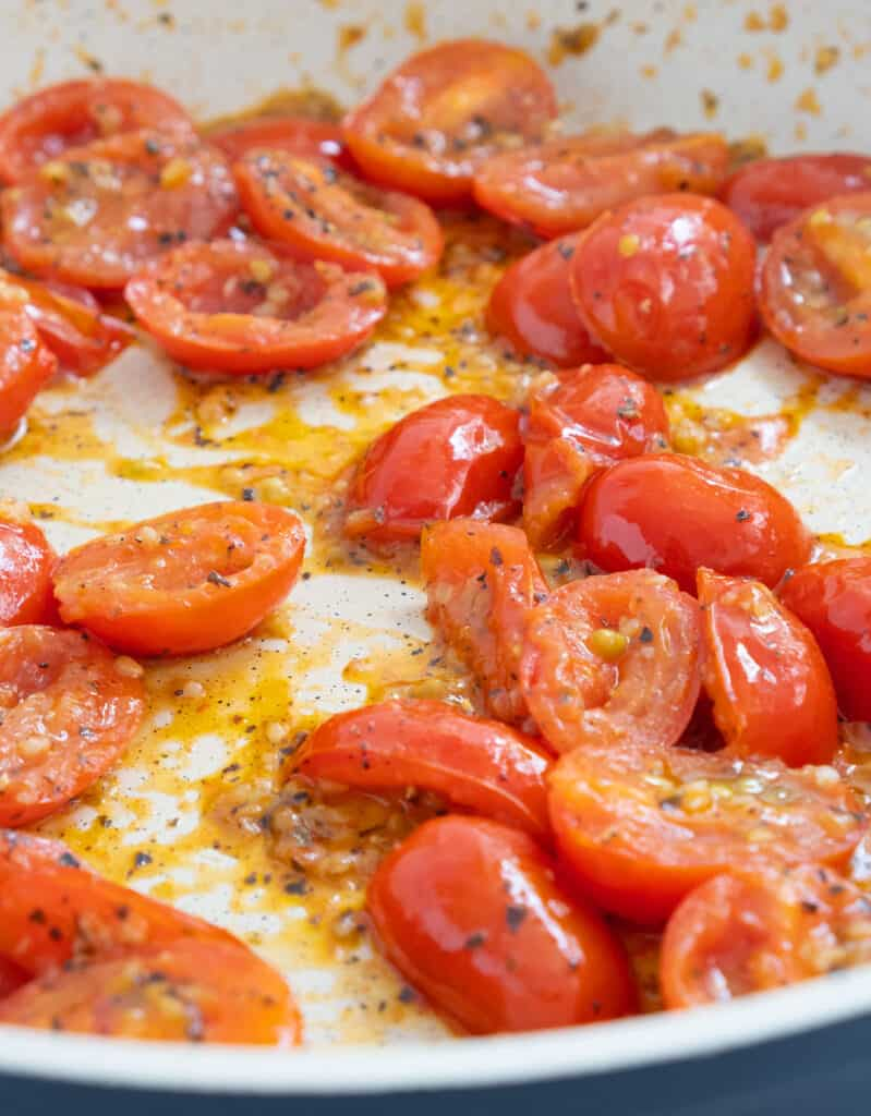 Close-up of some cherry tomatoes that realise their juice while cooking in olive oil with garlic and dried basil.