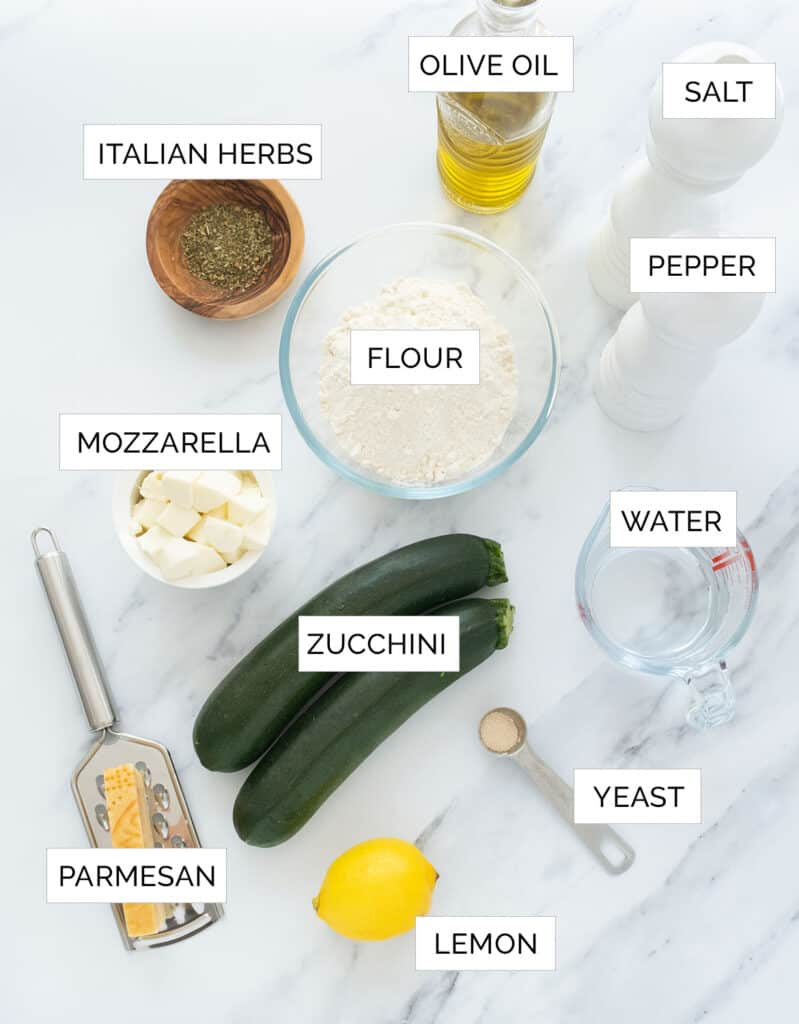 The ingredients to make this pizza with zucchini are arranged over a white marbled background.