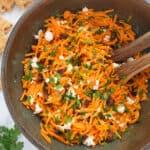 Top view of a brown salad bowl full of carrot raisin salad.