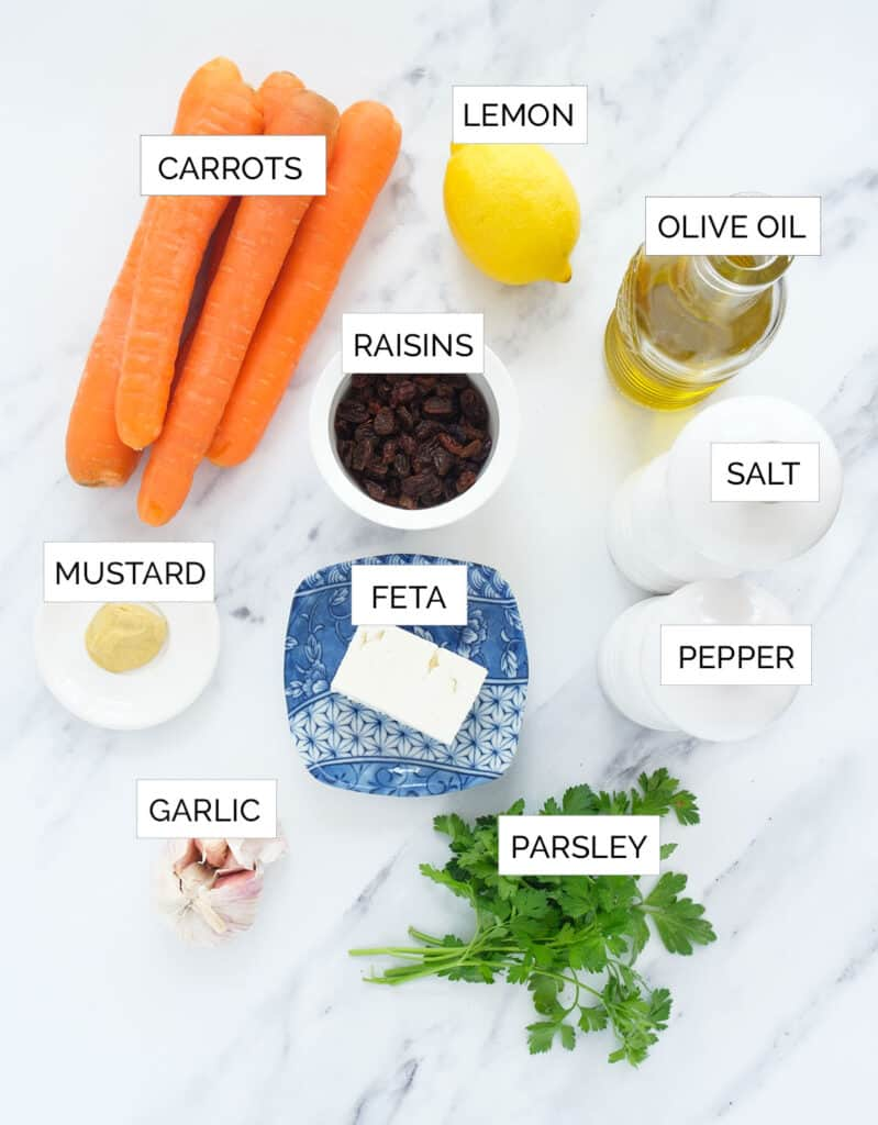 The ingredients to make this carrot raisin salad are arranged over a white background.
