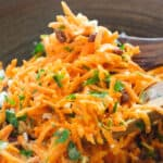 Close-up of two wooden spoons full of carrot raisin salad.