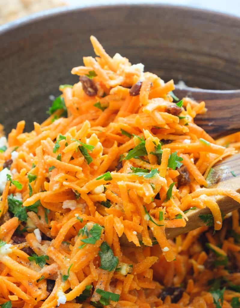 Two wooden spoon tossing carrot raisin salad.