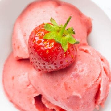 Close-up of a white bowl full of frozen strawberry yogurt topped with a fresh strawberry.