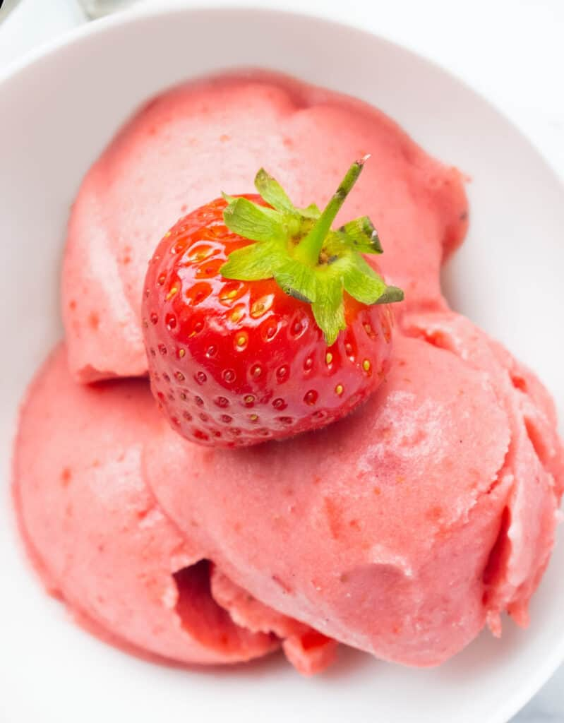 Close-up of a white bowl full of frozen strawberry yogurt topped with a whole strawberry.