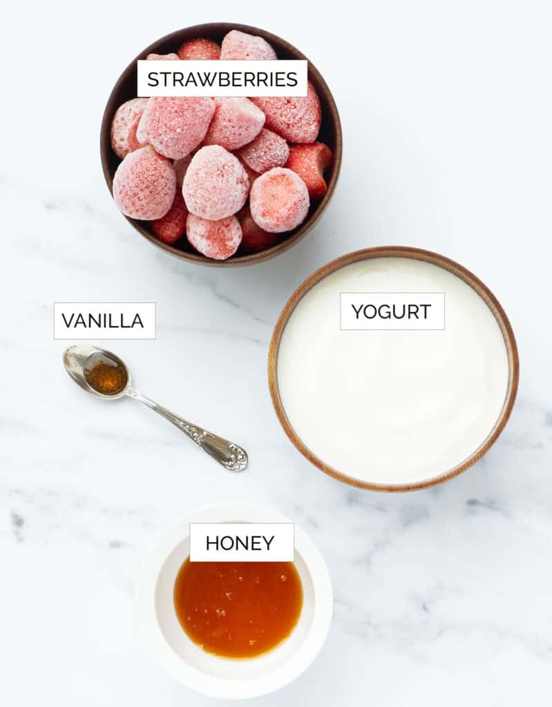 The ingredients to make the frozen strawberry yogurt are arranged over a white background.