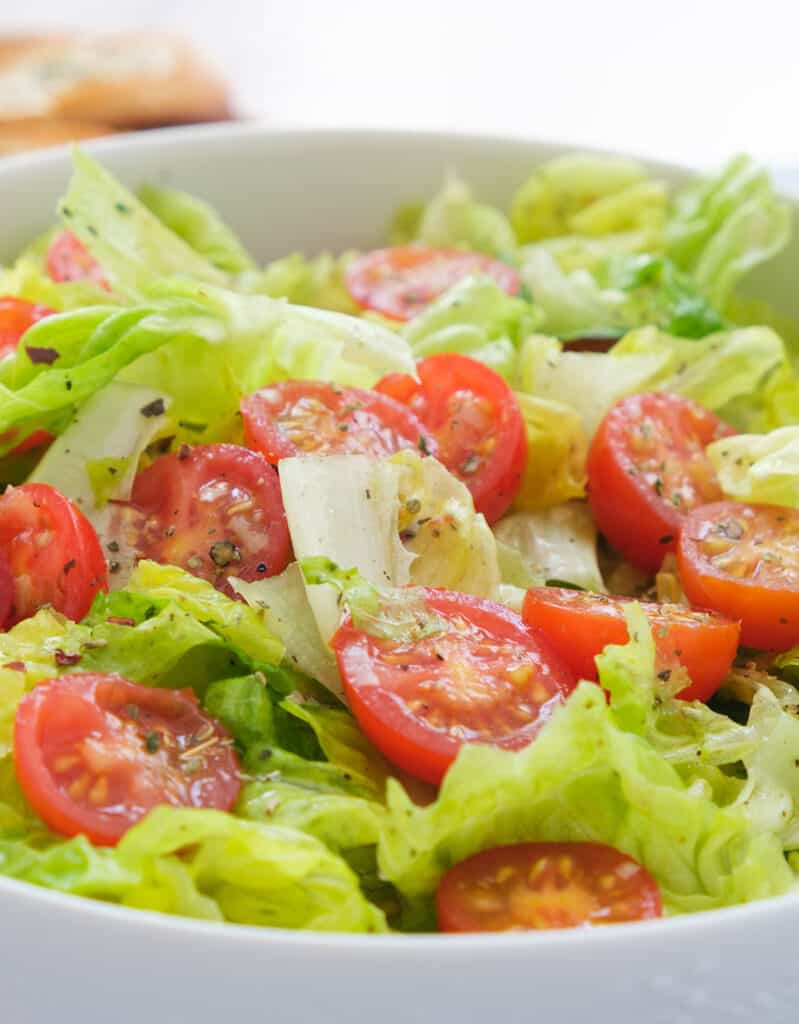 Close-up of a white bowl full of lettuce salad with cherry tomatoes.