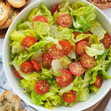 Top view of a white bowl full of lettuce salad and cherry tomatoes.
