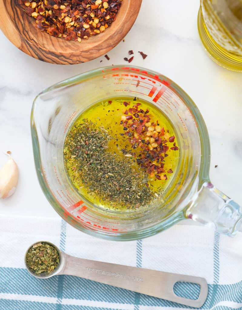 Top view of a glass jug full of lemon dressing with chili flakes.