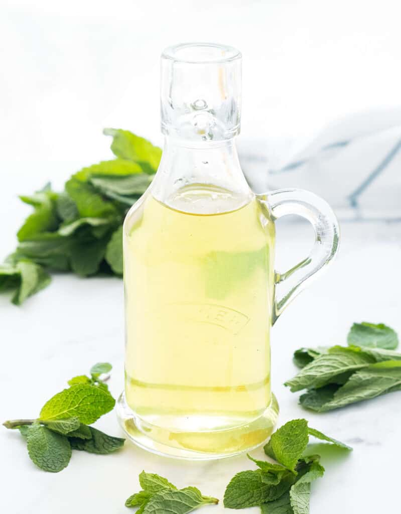 A small glass bottle full of mint syrup and mint leaves over a white background.
