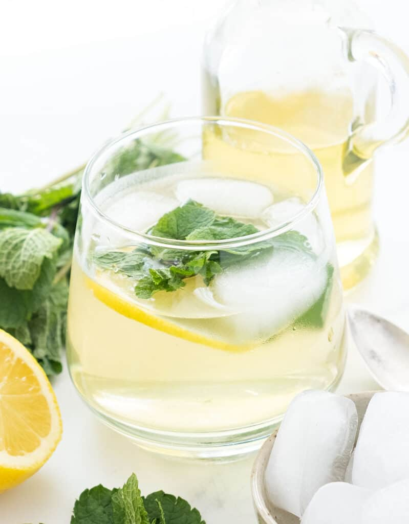 Close-up of a glass full of water, ice and mint surrounded by mint leaves and a bottle containing mint syrup.