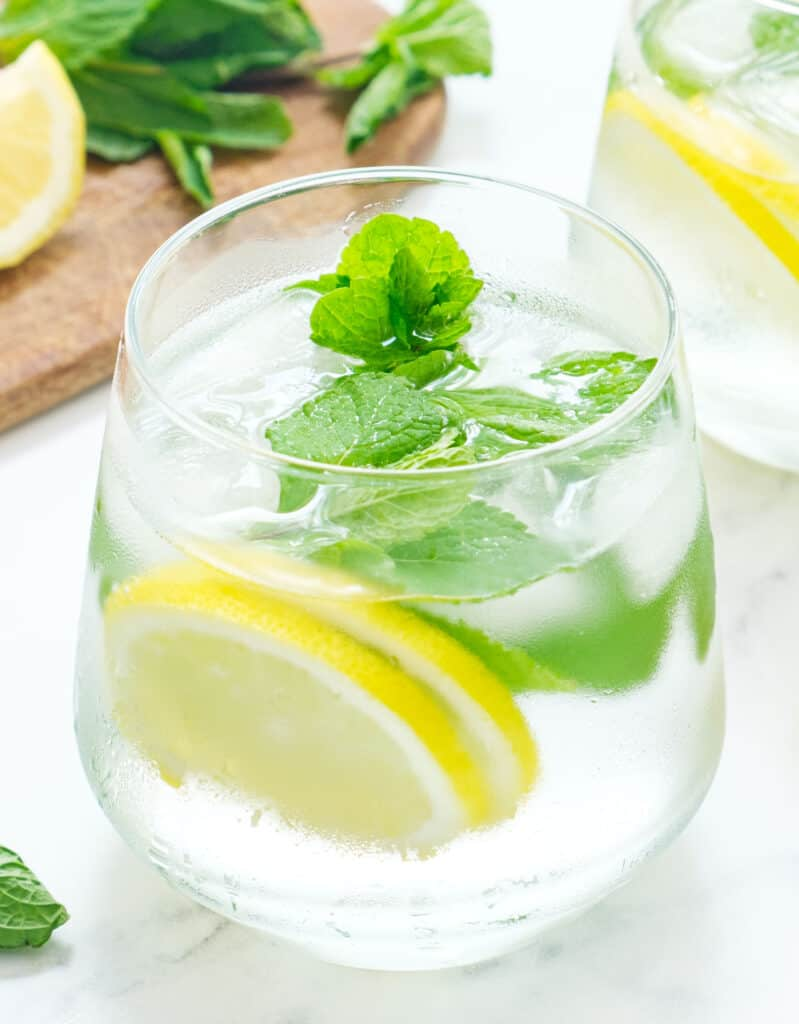 A glass of cold mint water with lemon slices and mint leaves.