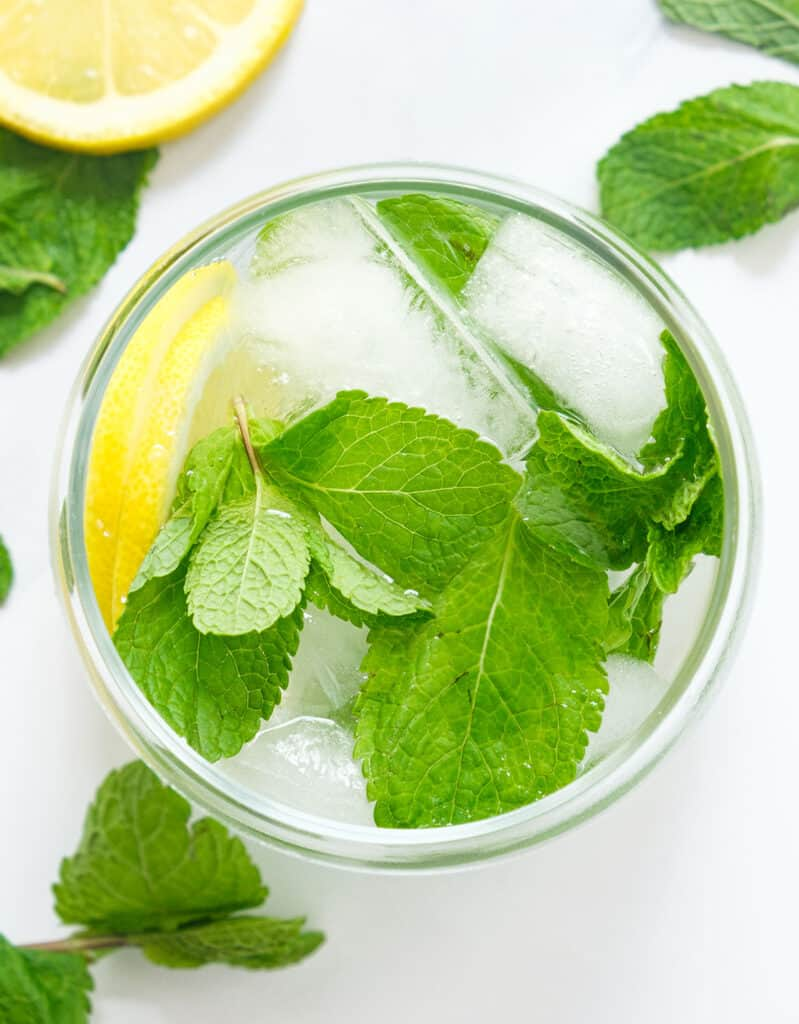 Top view of a glass full of infused water, ice and fresh mint leaves in the background.