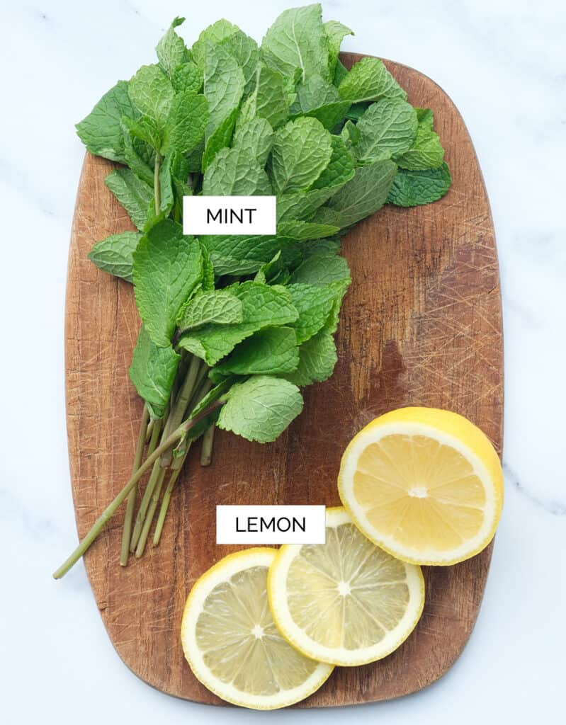 Top view of a wood chopping board with half lemon and a bunch of mint leaves.