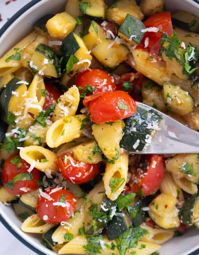 Close-up of a fork lifting some juicy pasta with tomatoes, zucchini and grated parmesan cheese.