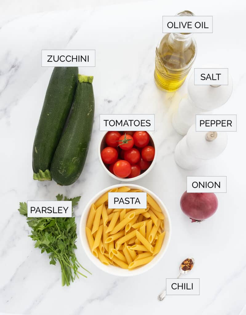 The ingredients to make this pasta with zucchini are arranged over a white background.