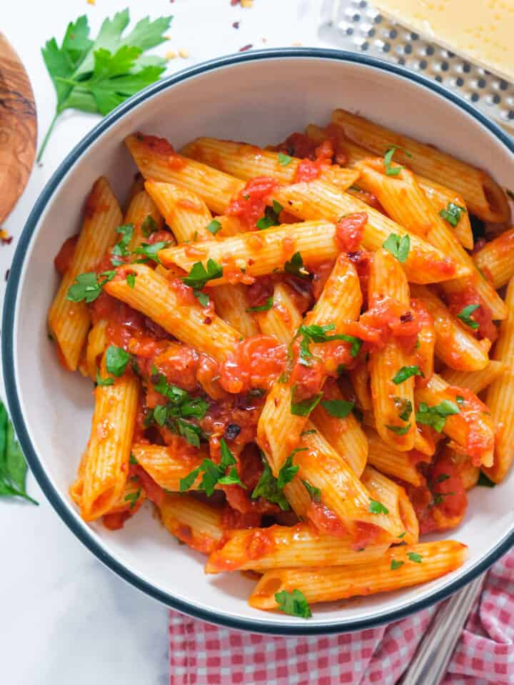 Top view of a white bowl full of penne arrabbiata.