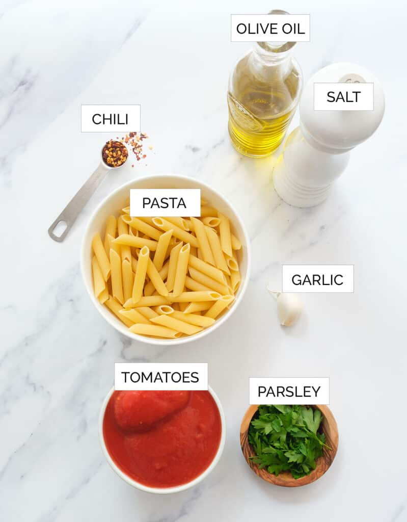 The ingredients to make penne arrabbiata are arranged over a white background.