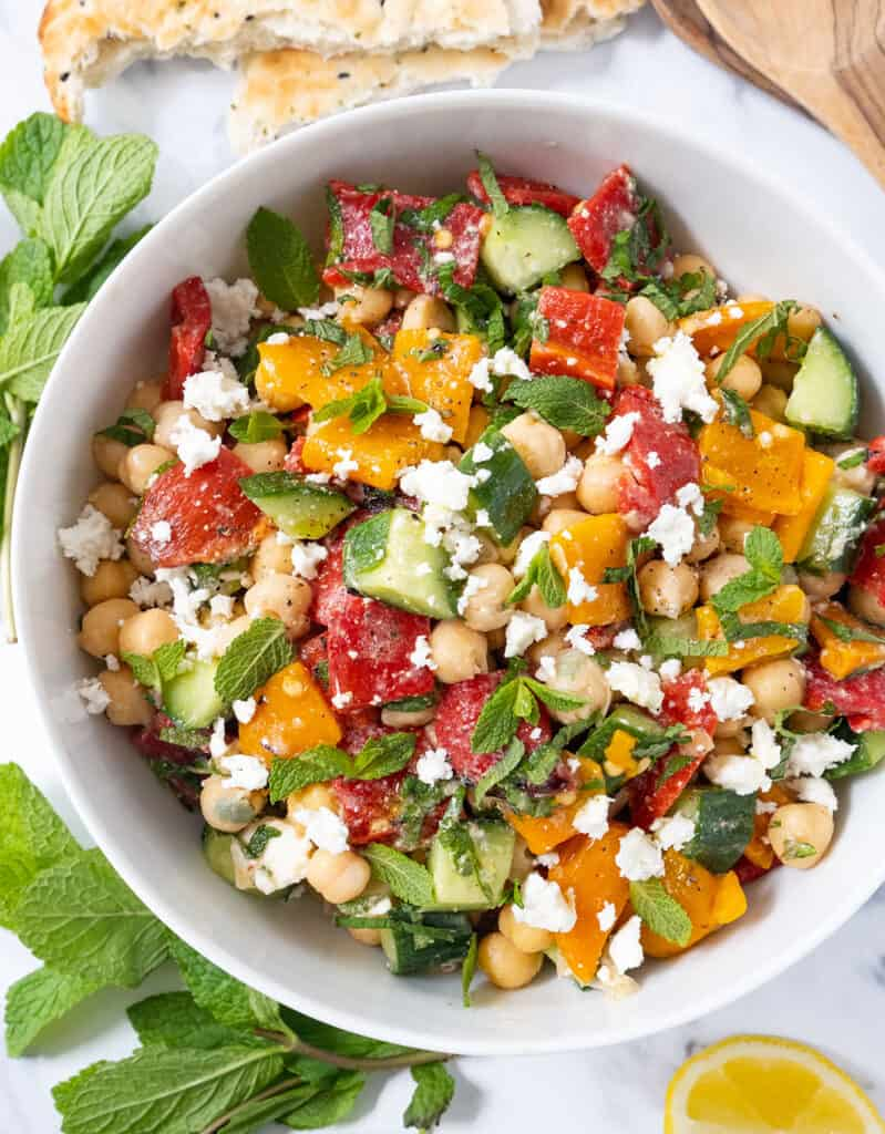 Top view of a white bowl full of salad with roasted peppers, chickpeas and fresh mint leaves.