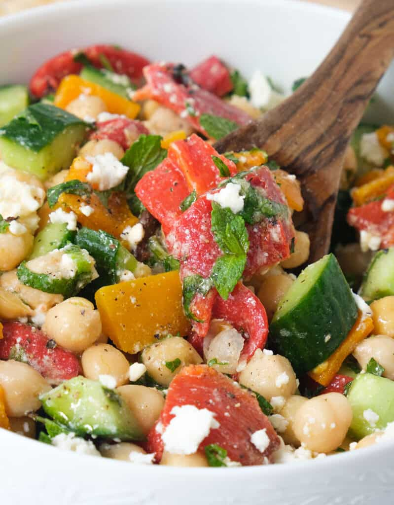 Close-up of a juicy salad made with roasted peppers, cucumber, chickpeas and plenty of mint leaves.