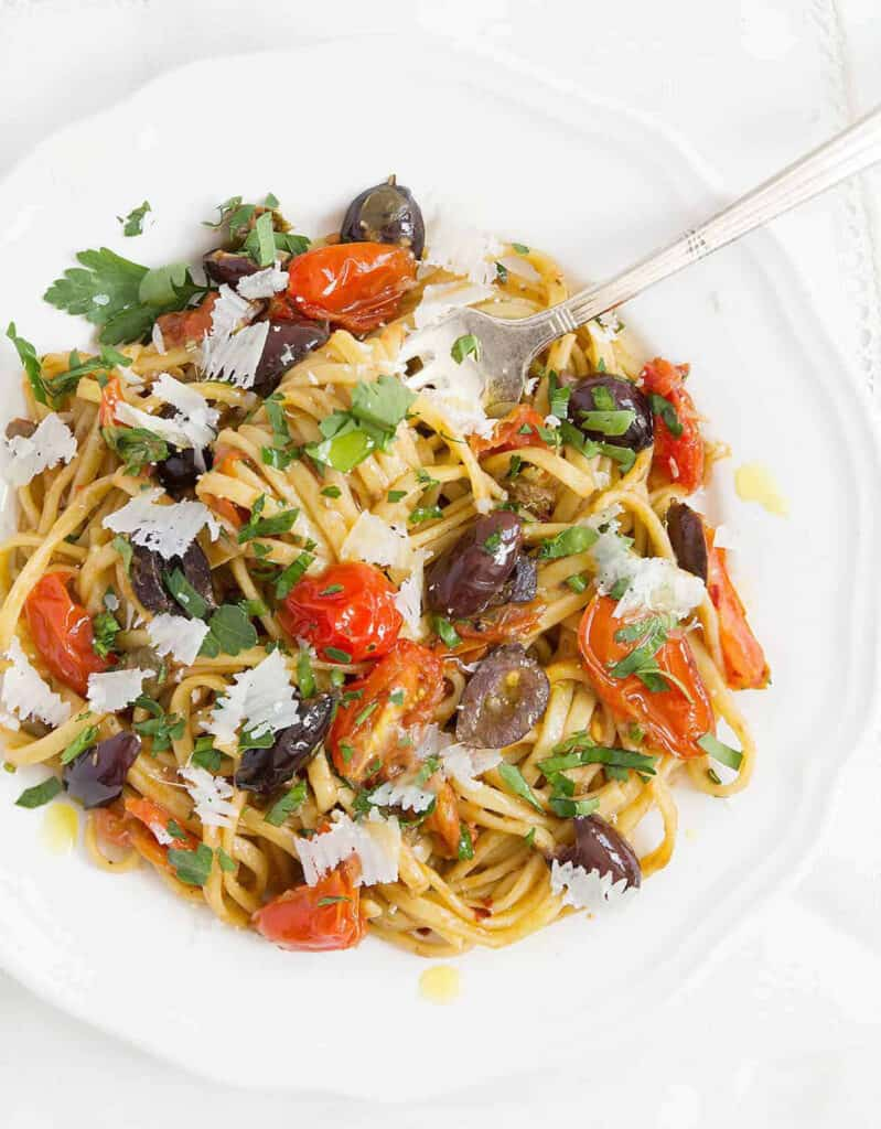 Top view of a white plate full of Italian spaghetti alla puttanesca with black olives and cherry tomatoes.